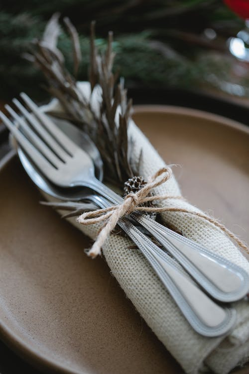 From above silverware spoons and forks in linen cloth decorated with herbs on ceramic plate