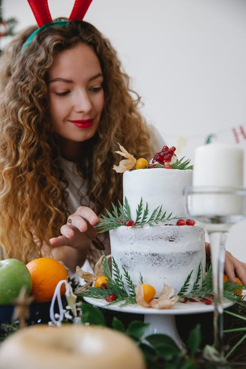 Beautiful woman with wavy hair decorating Christmas cake while preparing for party at assorted table with fruit and sweets