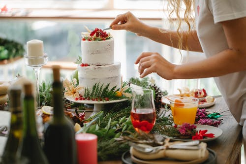 Crop anonymous female chef in casual clothes standing at table with various dishes and drinks and putting berries on top of delicious cake