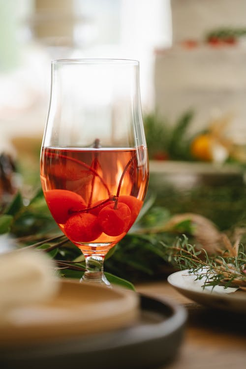 Glass of cherry wine on decorated table