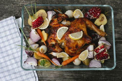 Delicious roasted chicken with assorted vegetables and fruits on table