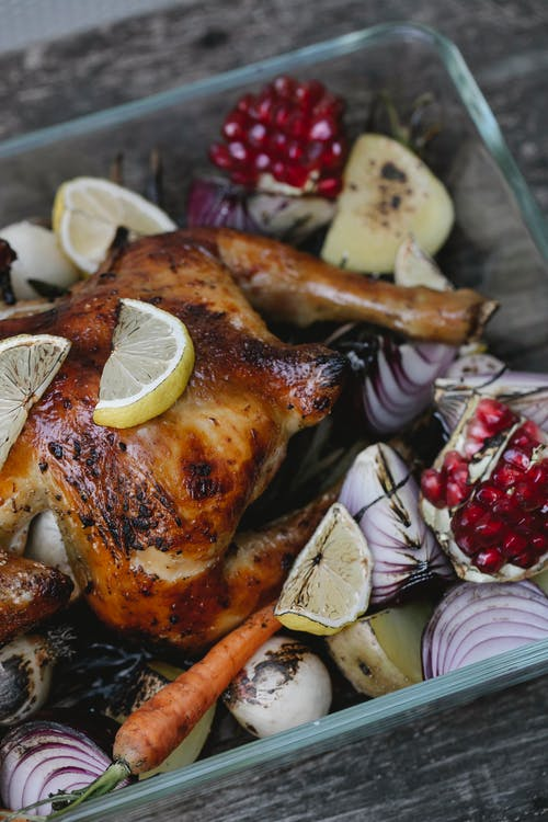 High angle of appetizing baked chicken with pomegranate seeds and lemon slices with red onions in baking dish
