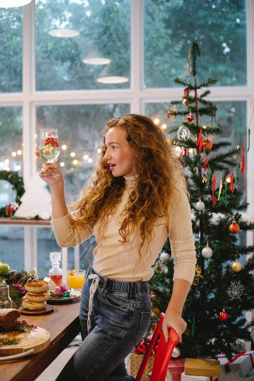 Amazed woman with champagne celebrating Christmas holiday at home