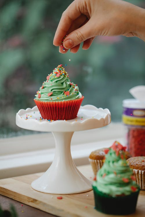 Crop anonymous cook sprinkling tasty cupcake with buttercream on stand while preparing for festive event in house