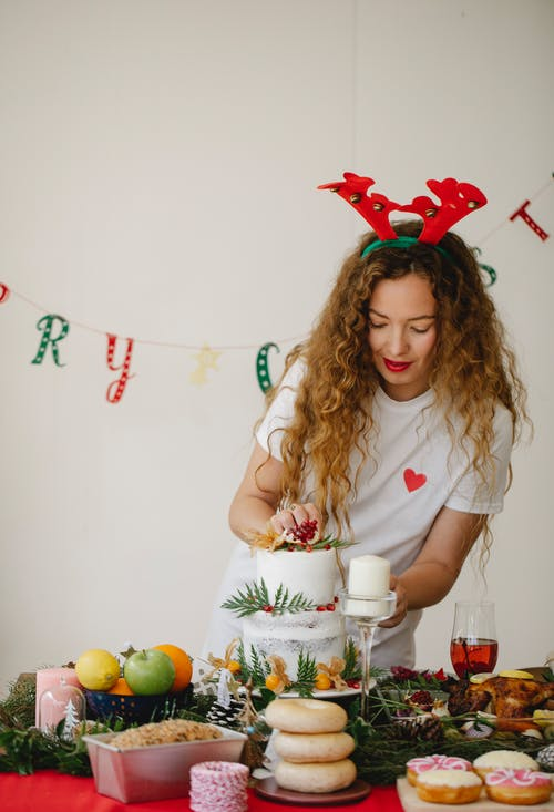 Woman decorating delicious cake on Christmas day in house
