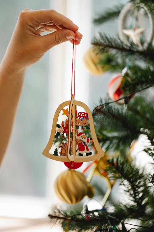 Woman decorating fir tree with toy