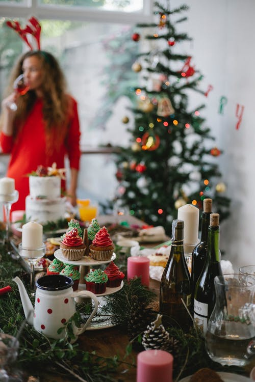 Female in antler headband drinking champagne standing near table with dinner for Christmas celebration and fir tree