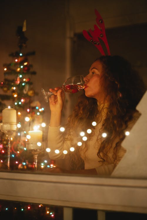 Through glass of female celebrating Christmas with glass of champagne in room with fir tree decorated with shiny garlands at night