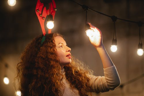 Surprised woman standing under glowing garland with bulbs