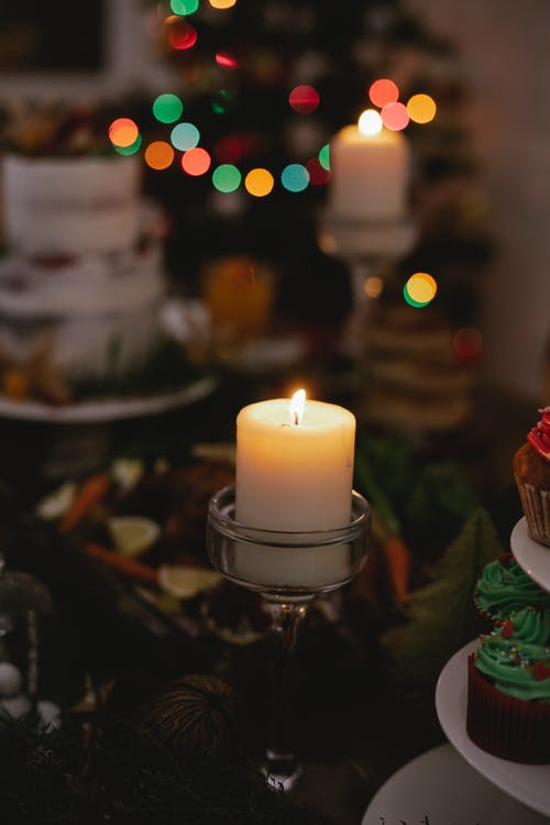 Festive dinner on table decorated with burning candle against fir tree with shining garland at Christmas Eve