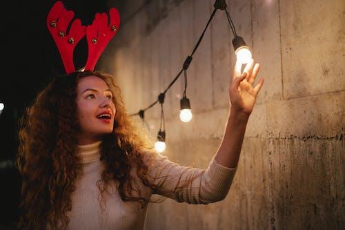 Amazed woman in deer rim touching light bulbs