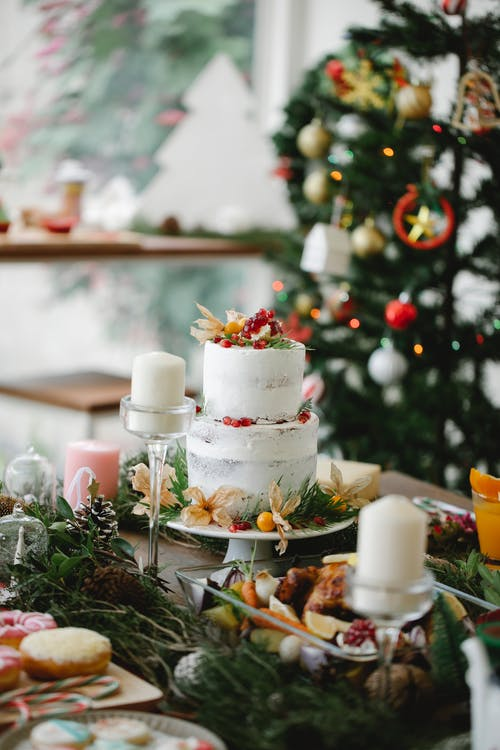 High angle of assorted delicious food and two tier cake decorated with twigs and berries on table for Christmas dinner
