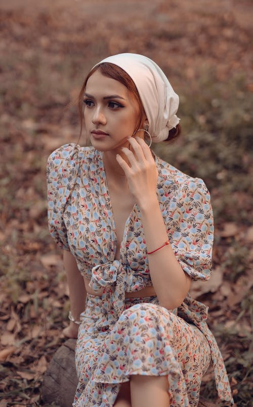 High angle of young thoughtful female in summer outfit touching cheek while sitting in countryside and looking away
