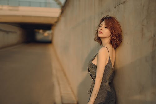 Side view of charming Asian female in trendy outfit leaning on wall with closed eyes