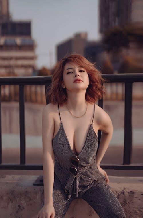 Stylish Asian woman sitting on embankment