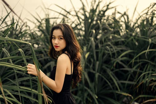 Asian lady standing in tall grass on green meadow