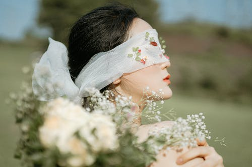 Faceless ethnic woman covering eyes with veil in nature