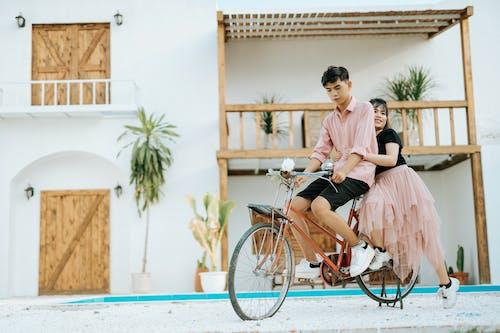 Couple on bike in street near cottage