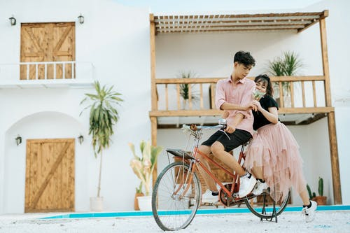 Full length of young ethnic couple in street hugging on bicycle while man giving flower near building with white wall and wooden doors with balcony in daylight in summer
