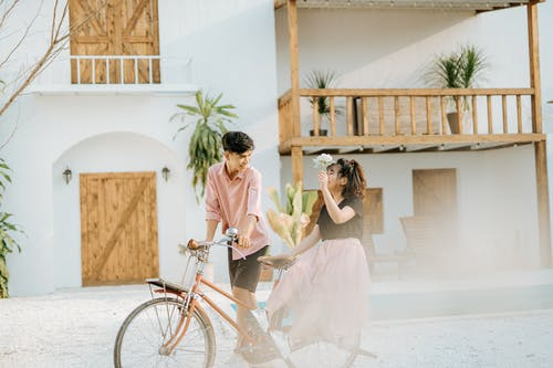 Couple spending time in street near building with white wall and wooden doors with balcony while man riding woman with flower on bicycle near plants and looking at each other