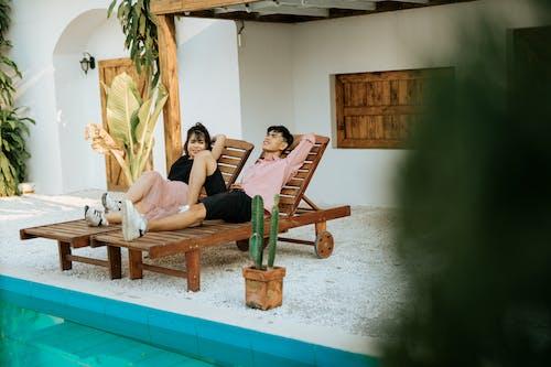 Couple on deckchair in street near villa and pool