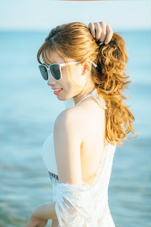 Charming woman touching hair standing in sea