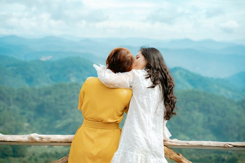 Asian traveler embracing anonymous mother against foggy mountains