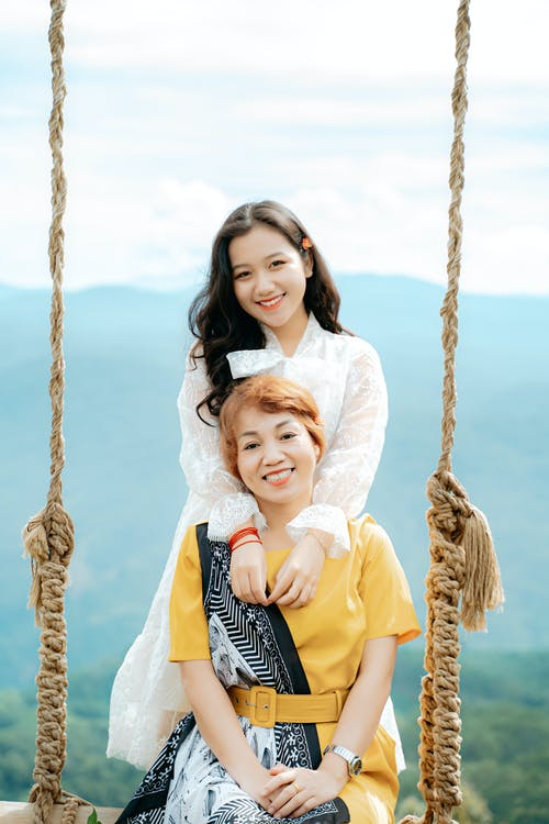 Young cheerful ethnic female embracing mom on swing with ropes while looking at camera against mountain