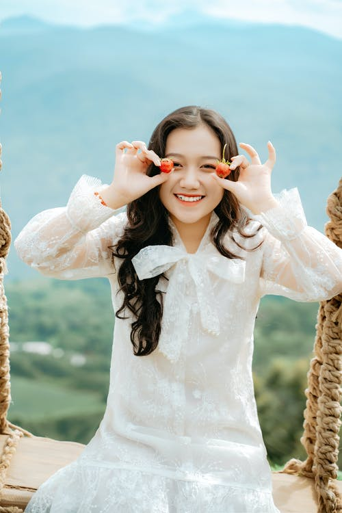 Young glad ethnic female in white outfit covering eyes with berries while looking at camera against mount