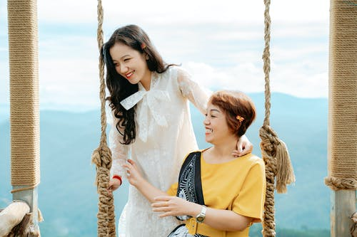 Smiling Asian daughter with mother on swing against mountain