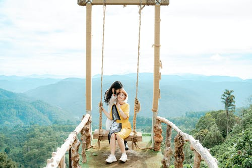Ethnic female traveler touching hair while kissing mom on swing against misty mounts under cloudy sky