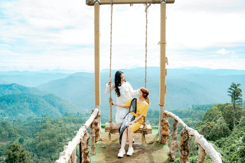 Content Asian female tourists speaking on bridge against foggy mounts under cloudy sky and looking at each other
