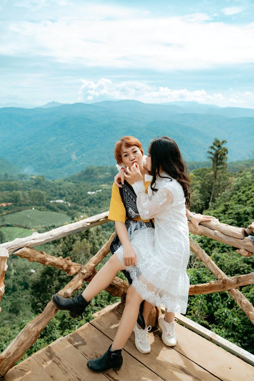 Asian mom with daughter having fun on bridge against mountains