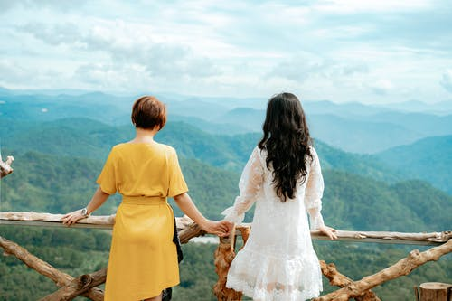 Back view of unrecognizable female tourists in dresses holding hands while admiring picturesque mounts during trip