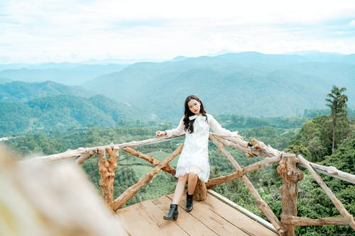 From above of confident young Asian female traveler in stylish outfit leaning on wooden railing of observation point during trip in picturesque green mountain valley