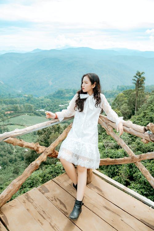 Peaceful young Asian lady admiring mountains on wooden viewpoint