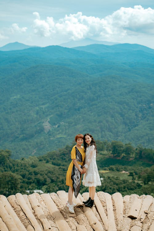 Cheerful young ethnic ladies holding hands and resting on viewpoint in mountainous valley