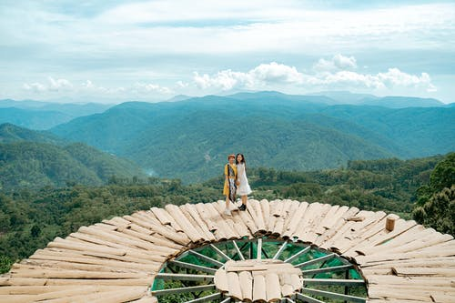 Side view of unrecognizable female travelers in stylish dresses standing together on creative wooden observation platform located in breathtaking green mountain valley