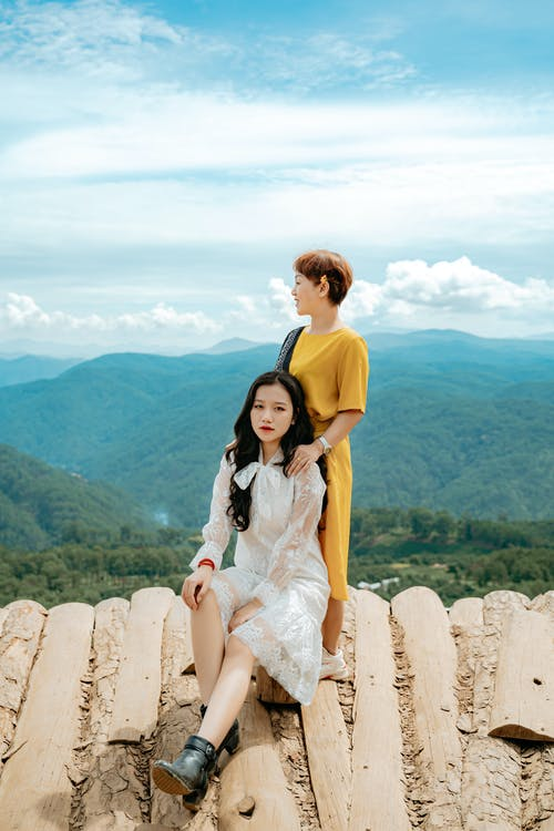 Calm young ethnic women resting together on viewpoint in picturesque mountain valley