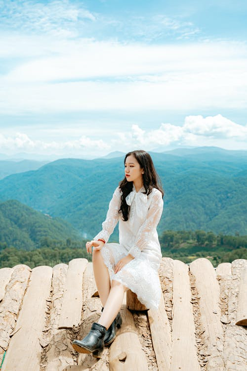 Pensive young Asian woman resting on roof edge and admiring green mountains