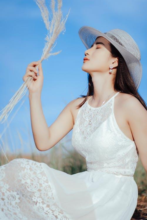 Femme En Robe Blanche Sans Manches Portant Un Chapeau De Soleil Blanc