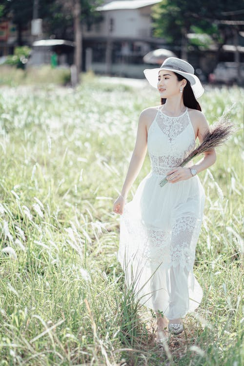 Young smiling Asian female in long white dress and white hat enjoying sunny summer day walking with beam of dry herbs in countryside