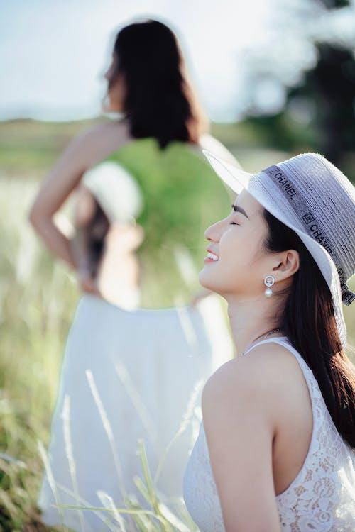 Romantic women in white dressers in sunny meadow