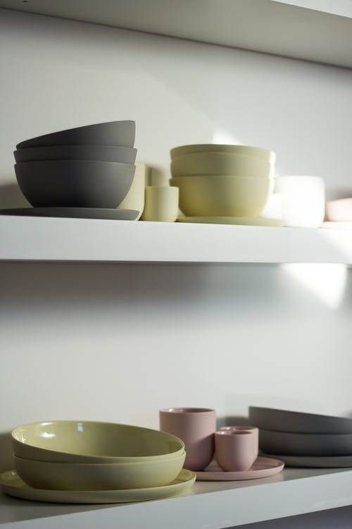 Crockery placed on shelves in modern kitchen