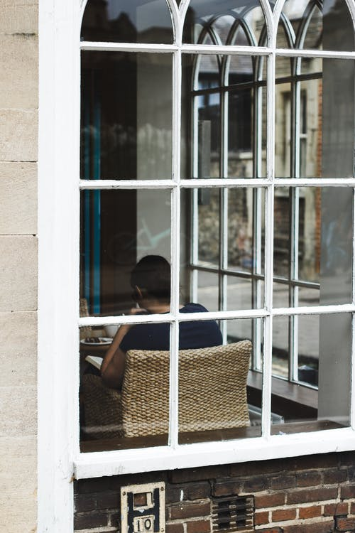 Unrecognizable person sitting in lobby behind building window