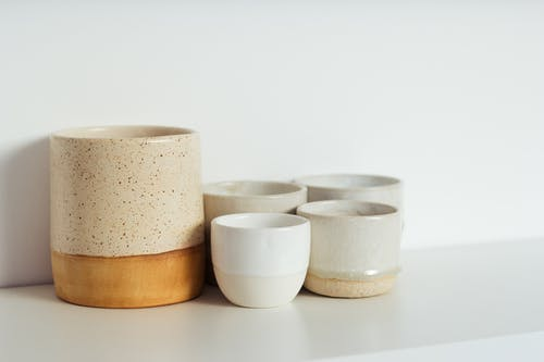 Collection of white and beige ceramic cups placed on shelf in light kitchen