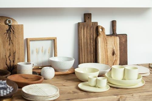 Set of minimalist light ceramic dishware and cutting boards arranged on wooden shelf in modern kitchen
