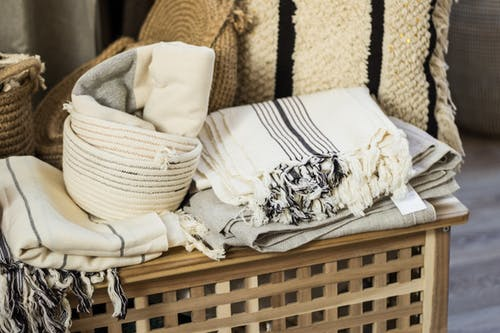 Stacked towels and plaid on wooden box