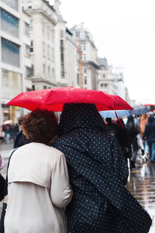 Back view anonymous females in coats under red umbrella strolling together on crowded city street during rainy autumn day