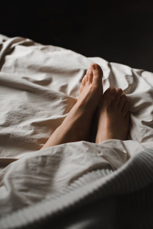 Crop anonymous barefoot female feet relaxing on soft comfy bed under white warm blanket in dark bedroom